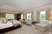Gorgeous master bedroom with fireplace offers his and her master baths