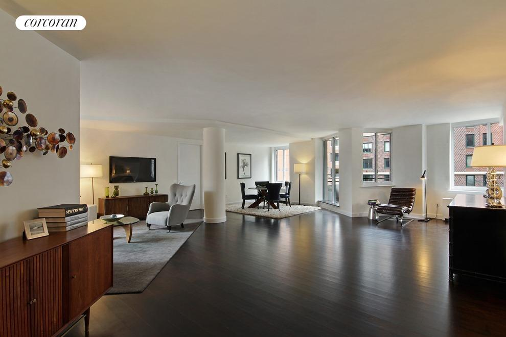 Enormous loft like living room features a private balcony featuring with partial views of the Hudson River, Jersey City skyline, and Rector Park.