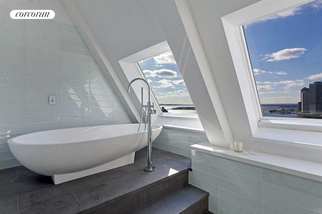 Imagine ending your day soaking in this monolithic bathtub overlooking the water and New York City from your penthouse apartment