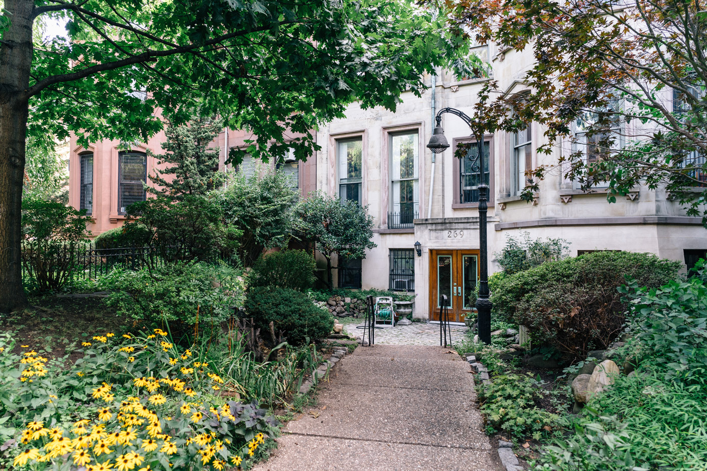 "White residential building with a small park in front in Clinton Hill"" style="
