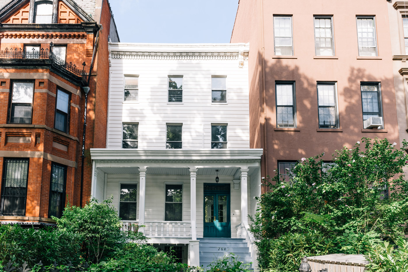 "Red brick, white wood, and brownstone residential buildings in Clinton Hills"" style="
