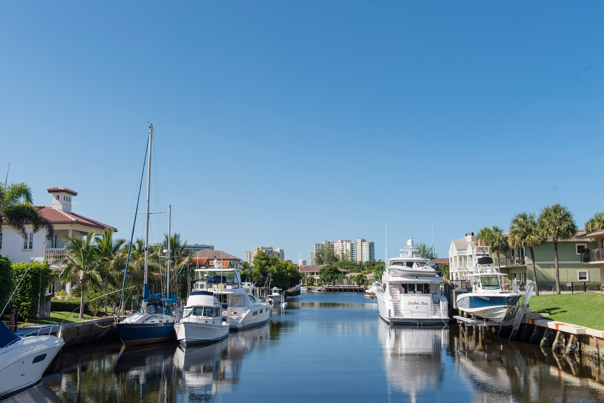 "A canal with waterfront houses and yachts in the water in Highland Beacht"" style="