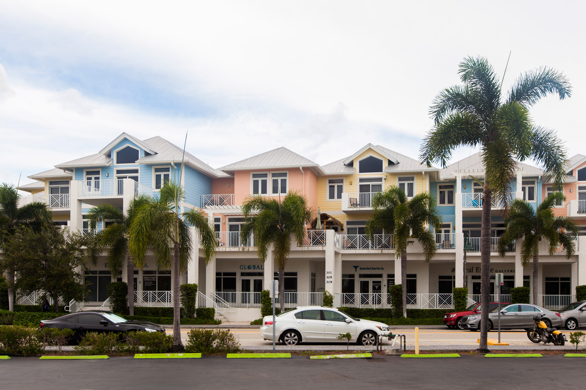 """Different colored buildings with businesses below and residential on top in Lantana """" style="""