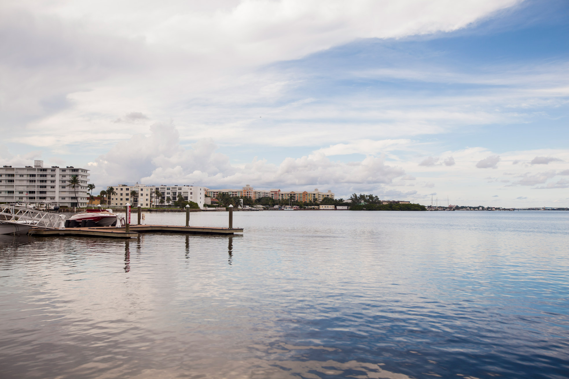 """A waterfront view of a docked boat and residential buildings in Lantana"""" style="""