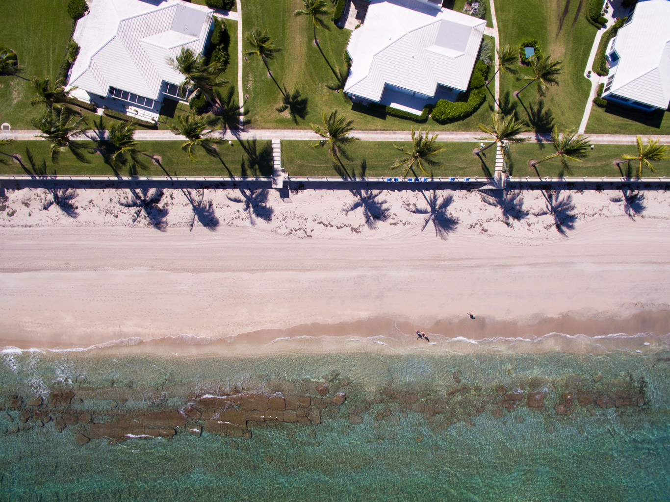 "An aerial view of some waterfront houses along the beautiful beach in Manalapant"" style="