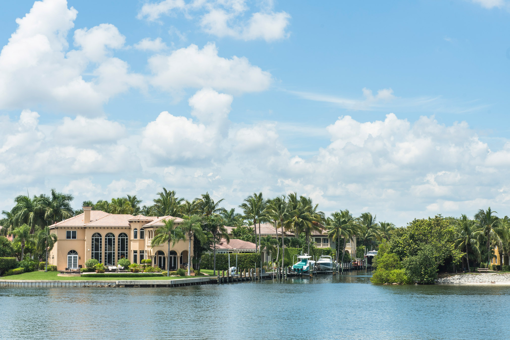 "Large beautiful waterfront houses with docked boats in North Palm Beach"" style="