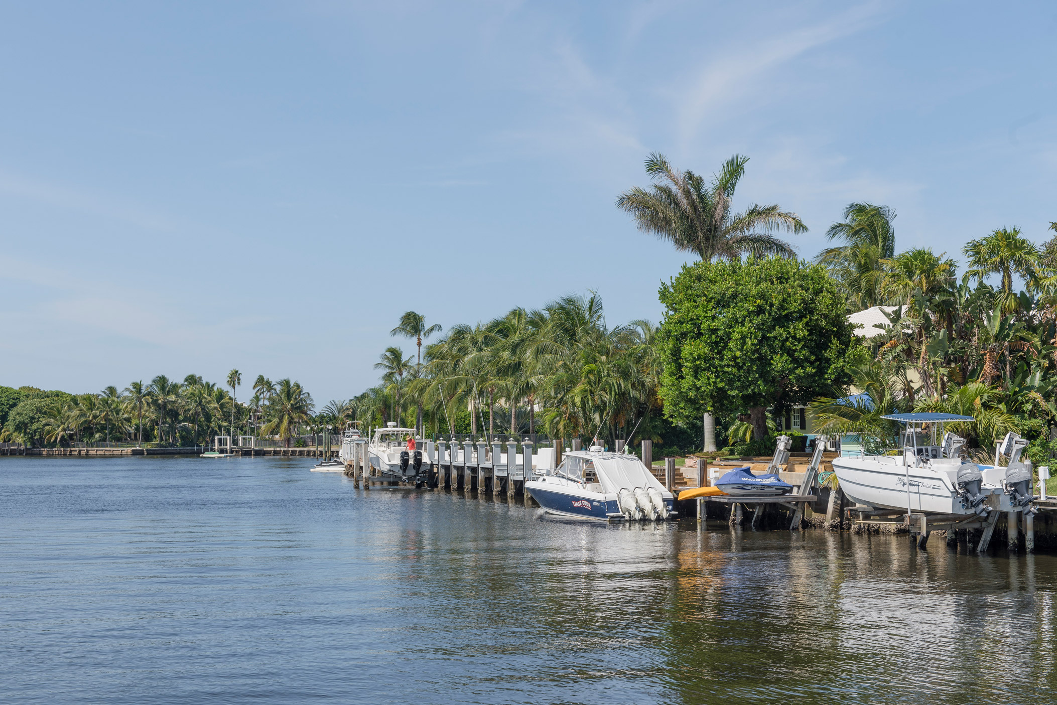 "Fishing boats docked at waterfront houses in Ocean Ridge"" style="